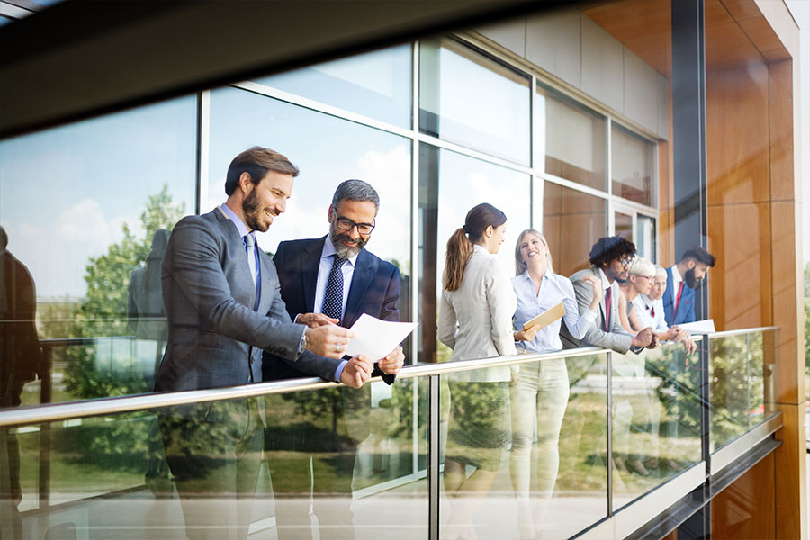 Blog - Businessmen Looking Over a Document in a Corporate Building Surrounded by People