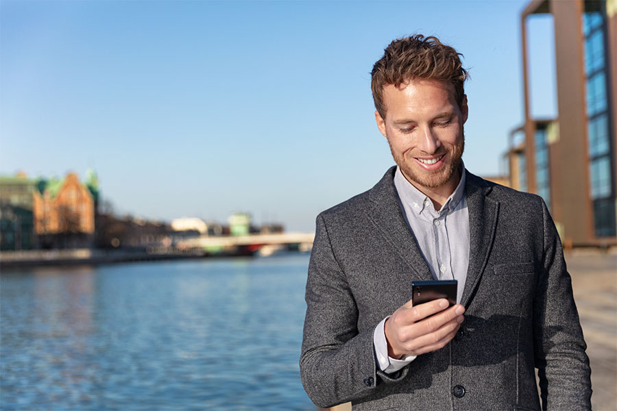 Client Center - Man Looking at His Phone in Front of a River and a Cityscape